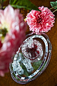 Liqueur in a crystal carafe on a silver tray beside a dahlia