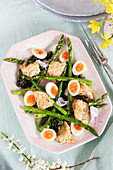 Grilled green asparagus with quail eggs, tapenade and bread