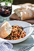 Lamb mince with vegetables, kidney beans and bread on an outdoor table