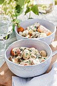 Lamb ragout with mushrooms and vegetables on summery table outdoors