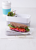 A wholegrain bread sandwich with beetroot cream and salmon (office lunch break)