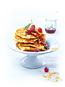 Yeast pancakes with raspberry sauce and almond flakes
