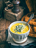 Creamy carrot soup served with sprouts and pumpkin seeds on a rustic background