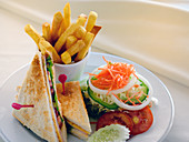 A club sandwich with a side salad and french fries