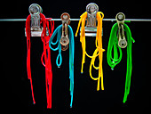 Different coloured spaghetti hung fom clips in front of a black background
