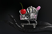A black hand holding a mini shopping cart filled with ice cubes and a cherry