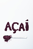 Acai berry powder: on a spoon and lettered against a white background