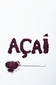 Acaipulver, auf Löffel und als Schriftzug vor weißem Hintergrund