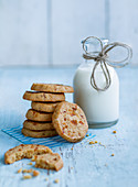 A stack of apricot biscuits next to a milk bottle