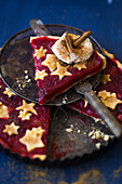 A slice of plum tart decorated with pastry stars, cream and cinnamon