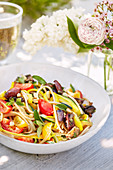 Spaghetti with tomatoes and olives on a summery table outdoors