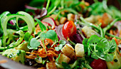 Mixed salad with a honey mustard dressing and herbs being made