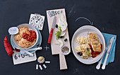 Spaghetti with tomato sauce and pasta with fish fillet, fennel and olives