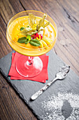 Mango sorbet decorated with citrus peel, mint, redcurrant in a glass with a red napkin and a spoon on a slate board and wooden background