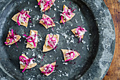 Crispy flatbread with mackerel pate and pickled red onion garnished with grated horseradish and red amaranth