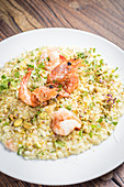 Sicilian pistachio and king prawns risotto with herbs on a white plate and a wooden background