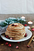 A stack of pancakes decorated with cranberries, tealights and pine springs