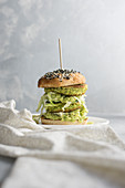 A burger with zucchini patties, cabbage and avocado cream