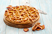 Apple tart with a lattice topping and pastry stars on a wooden plate