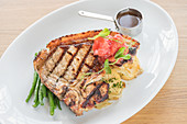 Grilled steak with long green beans, potatoes and grilled tomatoes with steak sauce on a white plate and light wooden background