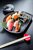 Japanese fresh mixed sushi platter with salmon, tuna, yellowtail, shrimp nigiri, salmon maki, tuna maki on a black plate and black table