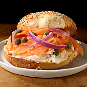 Salmon and cream cheese on sesame bagel with capers and red onions