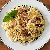 Engelshaarnudeln mit Schinken, Pinienkernen, getrockneten Tomaten und Basilikum