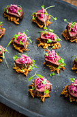 Canapes: crispy potato hash, venison and beetroot salad garnished with parsley leaves on a dark metal serving plate