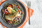 Gebratenes Lachsforellenfilet auf Linsensalat mit roter Zwiebel und Kirschtomatensalat