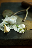 Garlic and thyme on a black chopping board