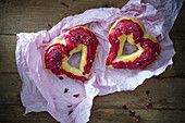 Oven-baked, heart-shaped vegan doughnuts with icing and rose petals