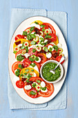 Caprese with olives and homemade rocket pesto