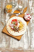 Tortillafladen belegt mit Schweinefleisch, Coleslaw und Gemüse
