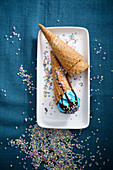 Blue vegan ice cream with chocolate sauce and sugar confetti in cones