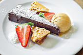 Moist and rich chocolate and honeycomb cake served with honeycomb, ice cream and fresh strawberries decorated with icing sugar