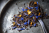 Loose leaf Earl Grey tea with dried citrus peel of lemon, orange and bergamot and blue cornflowers on a dark metal plate and a teaspoon