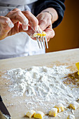 Italian chef making fresh homemade gnocchi pasta rolling on a fork and flour on the wooden board