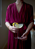 A woman in a dress holds a French 75 cocktail in her hands