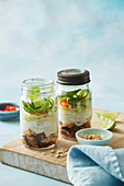 Chicken fillets with chilli jam, vermicelli and salad in glass jars