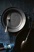 Schwarzer Teller mit Vintage Gabel, Pfanne und Löffel auf blauem Untergrund