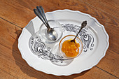 Bowls, spoons and jam on plate with feather pattern