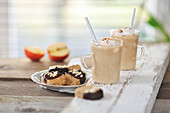 Baked apple smoothies with cream, and hazelnut biscuits with chocolate icing