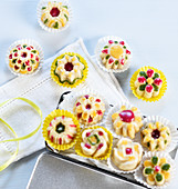 Mini cakes with colourful icing in paper cases (vegan)