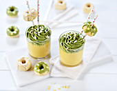Mango cream in glasses with matcha and white chocolate mousse, and mini doughnuts (vegan)