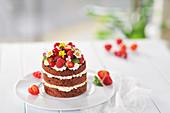 Veganer Mini-Naked-Cake mit Schokobiskuit, weißer Schokocreme, frischen Beeren und Blüten