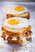 Croque Madame; Ham and Gruyere Cheese Grilled Sandwich with Herbed Aioli and Bechamel Sauce Topped with a Sunny Side Up Fried Egg