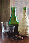 Red wine in a green carafe and a demijohn
