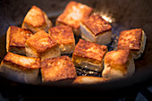 Fried tofu cubes in a wok (close up)