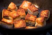 Fried tofu cubes in a wok (close up)