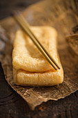 Fried tofu with chopsticks on paper (Asia)